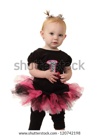 A one year old in tutu with pig tails is curious about you isolated on white