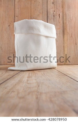 A open white fabric sack bag on wooden table