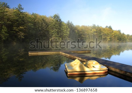 A paddle boat at dock reflected in a beautiful mountain lake at sunrise - stock photo