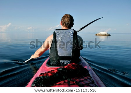 A paddler explores the scenic rock formations of the islands of Lake Malawi, Malawi, Africa, in his kayak. - stock photo