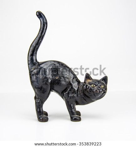 A painted black sculpture in the shape of a cat against a white background