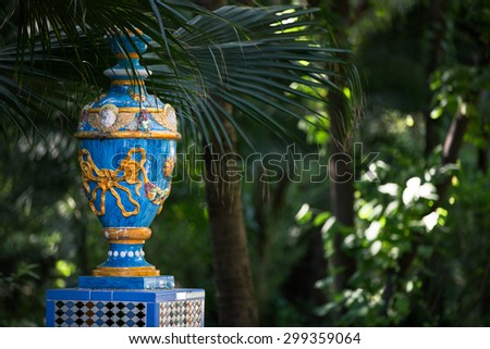 A painted vase in the lush vegetation of a public park in Seville, Spain - stock photo