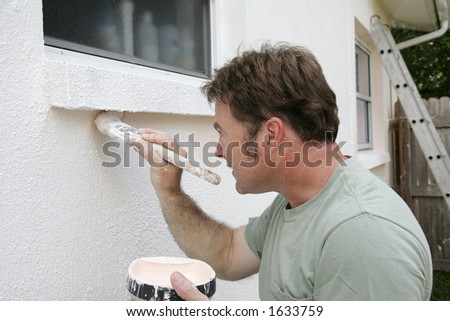 A painter edging around an exterior window with a brush. - stock photo