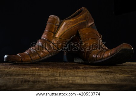 A pair brown leather shoes with on a wooden floor
