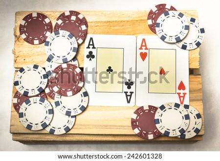 A pair of aces together with a pile of chips on a wooden support - stock photo