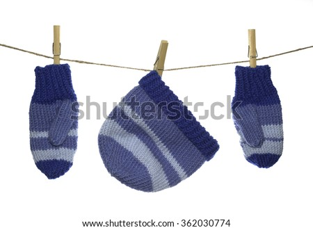 A pair of beautiful and warm handcrafted mittens and a matching hat hang by clothespins from a piece of twine.