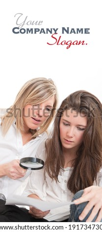 A pair of beautiful young women examining a document thou a magnifying glass  - stock photo