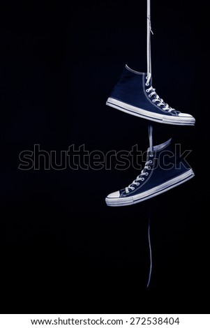 A pair of black and white sneakers tinted blue hanging by their laces in front of a black background - stock photo