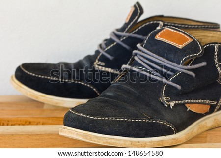 A pair of black canvas sneakers on the wood shelves . - stock photo