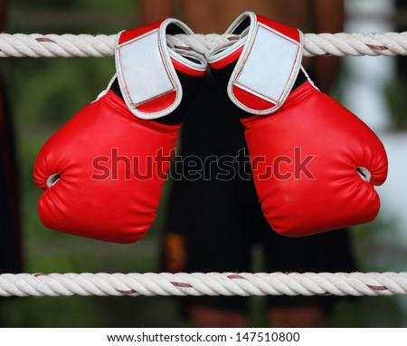 A pair of bright red Muay Thai boxing gloves hangs off the Boxing ring ropes - stock photo