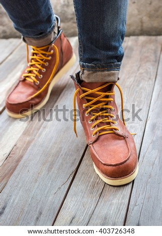 A pair of brown leather boots with laces placed on wooden floor, - stock photo