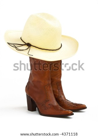 a pair of brown leather cowgirl boots and a straw western hat - stock photo