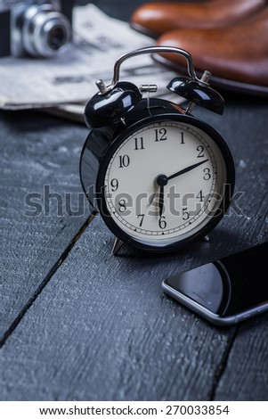 A pair of brown leather shoes with phone and clock on a black wooden floor - stock photo
