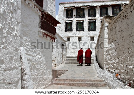 A pair of Buddhist monks walk through a monastery in rural Tibet. - stock photo