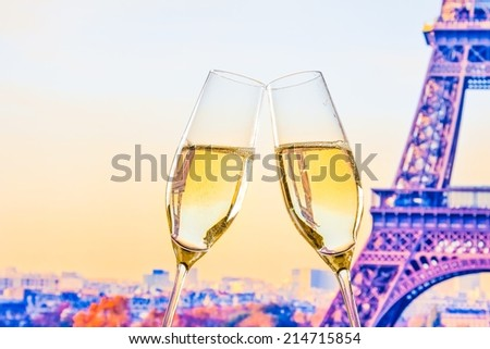 a pair of champagne flutes with golden bubbles make cheers on blur tower Eiffel background valentine day concept - stock photo