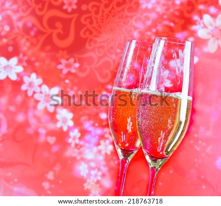 a pair of champagne flutes with golden bubbles on red vintage background love concept - stock photo