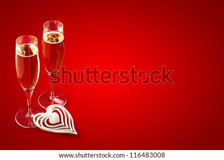 a pair of champagne glasses on red background - stock photo