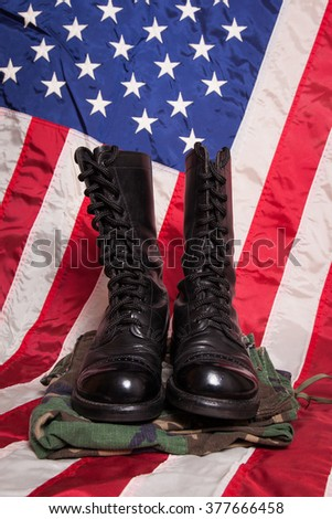 A pair of combat foots and camouflage pants with an American Flag. - stock photo