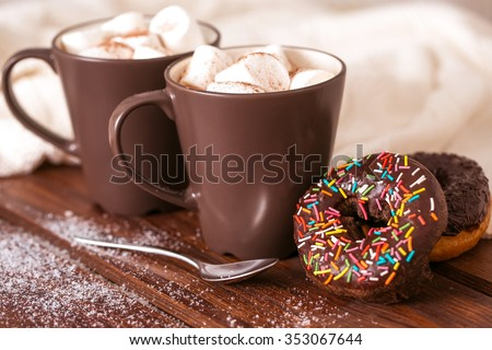 A pair of cups with cocoa, marshmallows and donuts with sprinkles - stock photo
