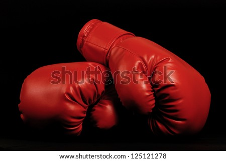 A pair of dark red vintage boxing gloves on black background - stock photo