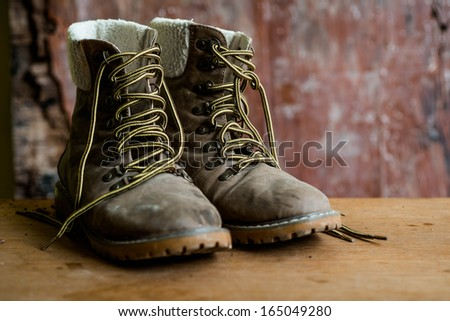 A pair of dirty boot on wooden background - stock photo