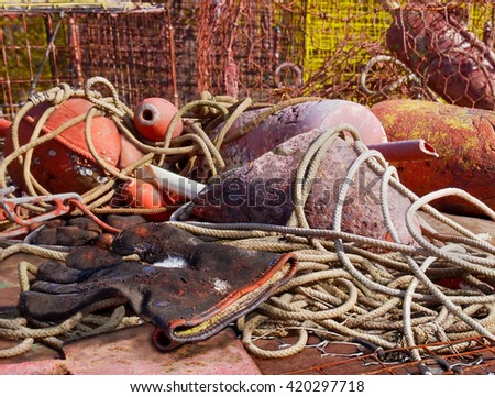 A pair of dirty old work gloves for painting is discarded among a pile of ropes, fishing buoys, and crab pots. - stock photo