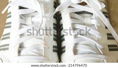 a pair of dirty sneakers isolated on white  - stock photo