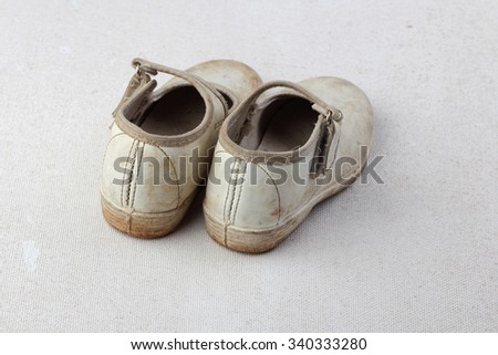 A pair of dirty white canvas shoe on a white surface - stock photo
