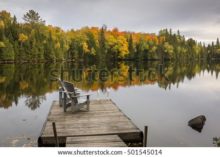 A pair of empty chairs sit on a dock on an autumn lake - Ontario, Canada