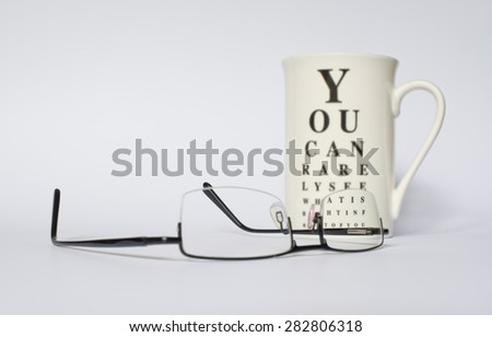 A pair of eye glasses in front of a mug with funny eye chart. Mug is blurry except the portion where the eye glass lens is. - stock photo