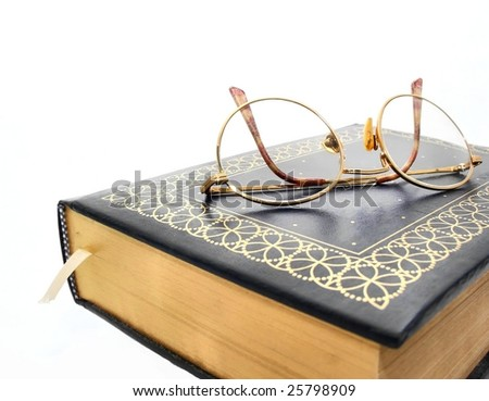 A pair of eyeglasses sitting on top of a book - stock photo
