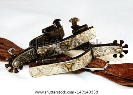 A pair of fancy, engraved western spurs with spur leathers in a high contrast white environment (shallow focus on upper spur). - stock photo