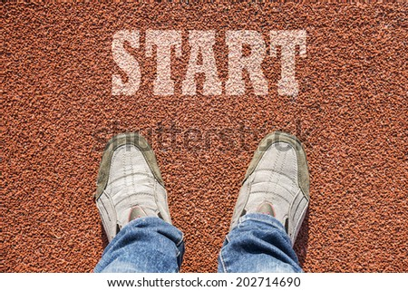 A pair of feet on a running track rubber with white print of the word START, concept of starting point. - stock photo