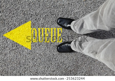 A pair of feet on a tarmac road with imprint of a yellow arrow and the word Queue for the concept of get in the queue.  - stock photo