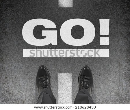 A pair of feet on a tarmac road with the word go. A concept of starting point.  - stock photo