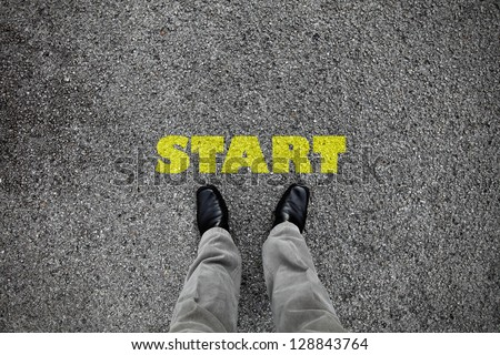 A pair of feet on a tarmac road with yellow print of the word start for the concept of starting point. - stock photo