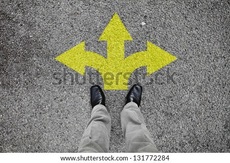 A pair of feet standing on a tarmac road with yellow arrow print pointing in three different directions for the concept of making decision at the crossroad. - stock photo