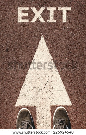 A pair of feet standing on street, white direction arrow, exit concept. Toned concept , low contrast. - stock photo