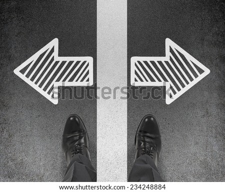A pair of feet standing on the road with drawn arrows in two different directions. Decision making concept.  - stock photo