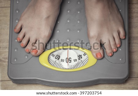 A pair of female feet standing on a scale