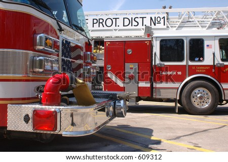 A pair of fire trucks lined up in a parking lot after Katrina. Taken in Slidell, LA, one with the American flag painted on its grill - stock photo
