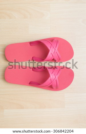 A pair of flip flops on wooden surface background