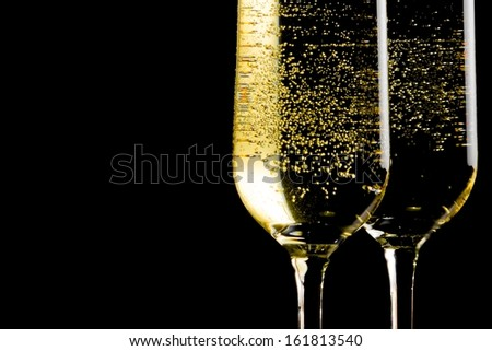 a pair of flutes of champagne with golden bubbles on black background and space for text - stock photo