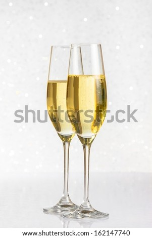 a pair of flutes of golden champagne on silver bokeh background on table - stock photo