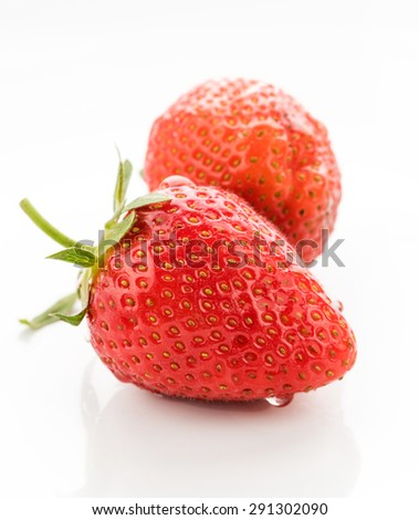 A pair of freshly washed strawberries on a high-key white background