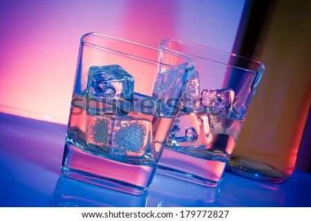 a pair of glasses of alcoholic drink with ice on disco violet light on white table