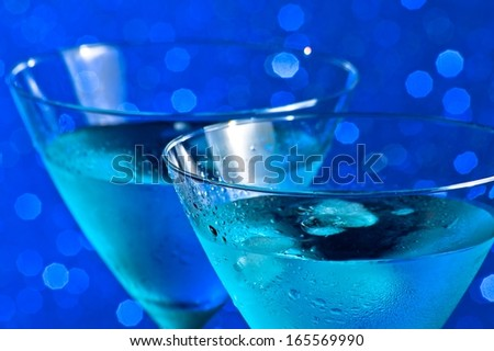 a pair of glasses of  fresh blue cocktail with ice on blue tint light bokeh background