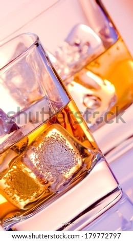 a pair of glasses of whiskey with ice on  disco violet light  on bar table