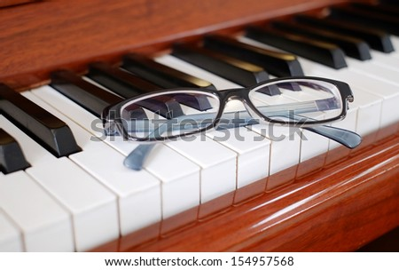 A pair of glasses on a piano - stock photo