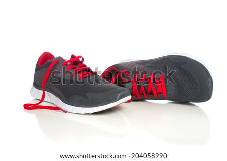 A pair of gray running shoes with red shoelaces on a white background - stock photo